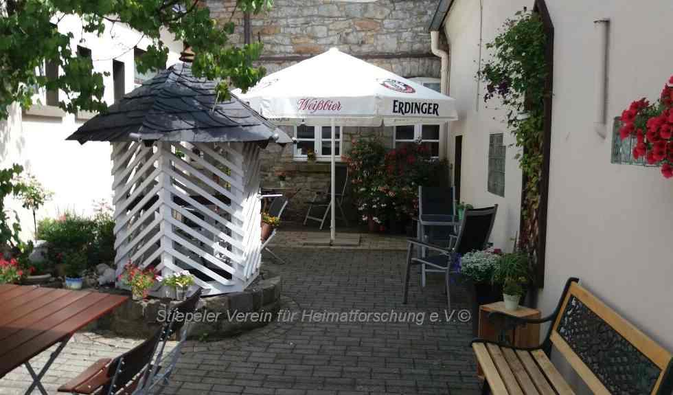 Der Innenhof mit der in Ruhrsandstein gemauerten Wand, Biergarten und Brunnen
