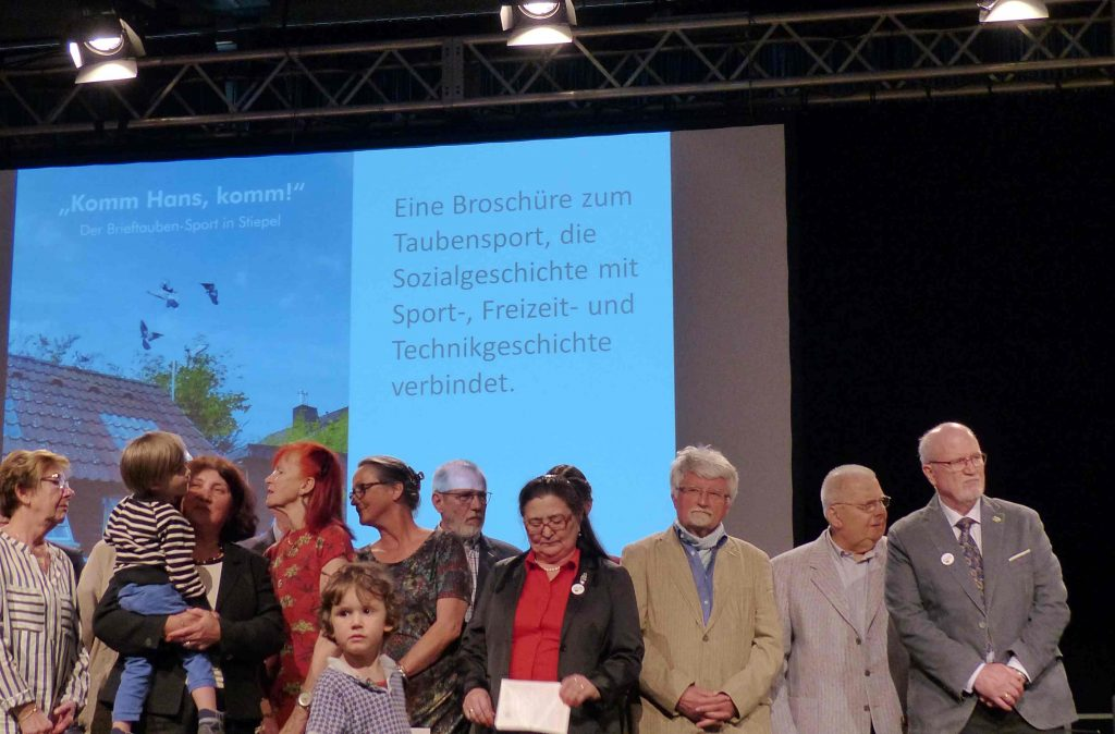 Vereinsmitglied Gerhard Hagenkötter (ganz rechts), im Hintergrund die Broschüre