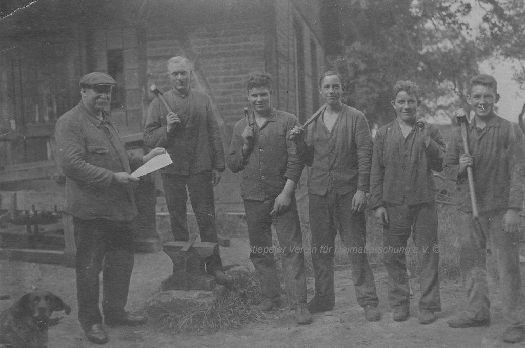 Vater und Sohn Gathmann mit Gesellen vor der Schmiede, 1920er Jahre